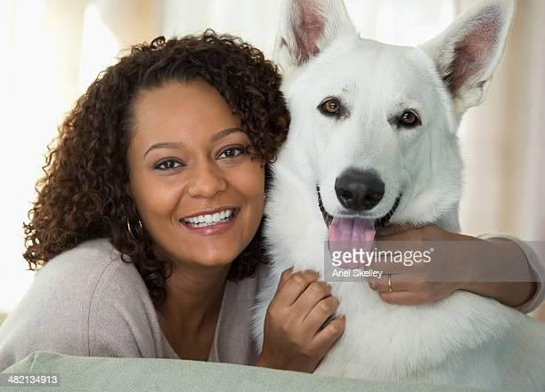 Mixed race woman petting dog