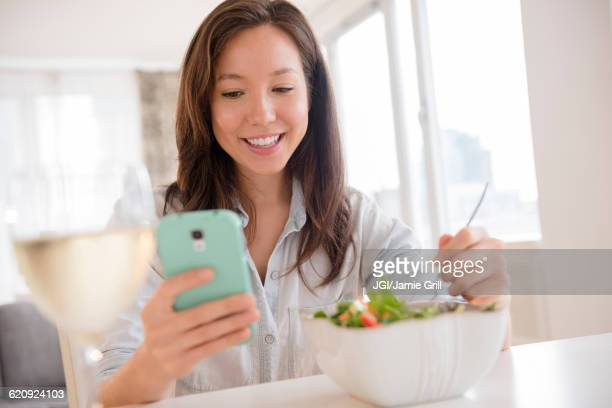 Mixed race woman photographing salad