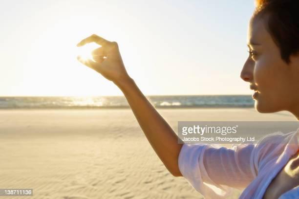 Mixed race woman pinching sun on beach