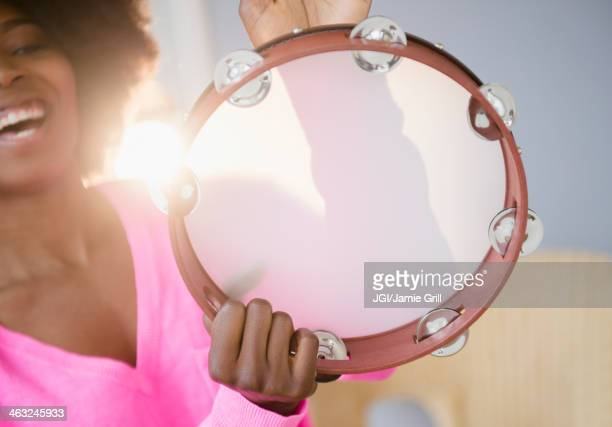 Mixed race woman playing tambourine