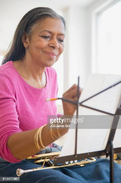 Mixed race woman playing trumpet