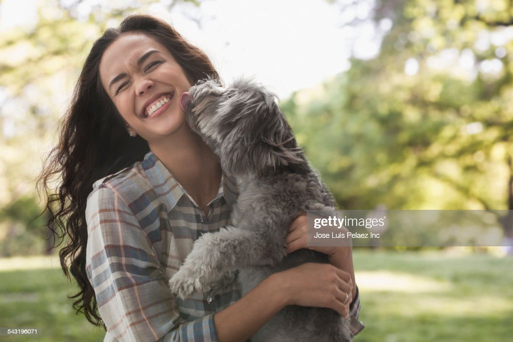 Mixed race woman playing with dog in park : Stock Photo