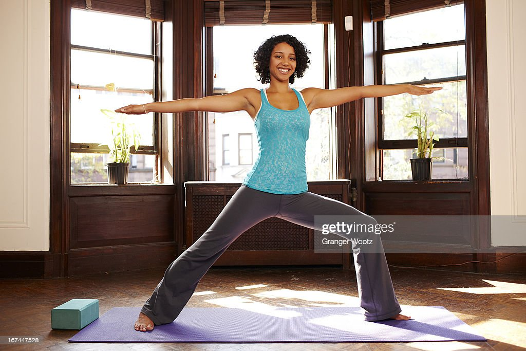 Mixed race woman practicing yoga in living room : Stock Photo