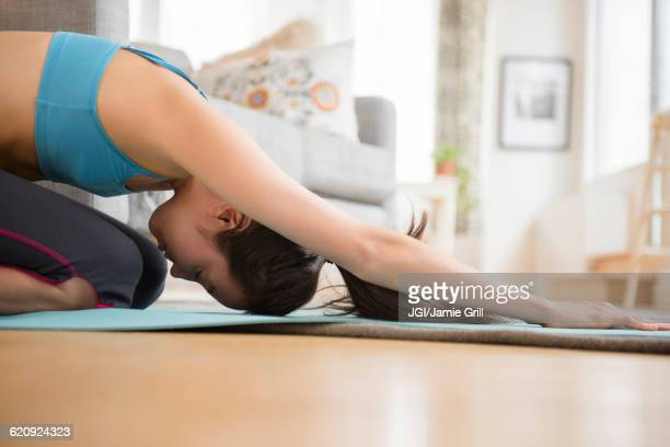 Mixed race woman practicing yoga in living room
