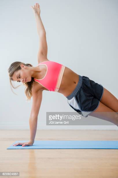 Mixed race woman practicing yoga in studio