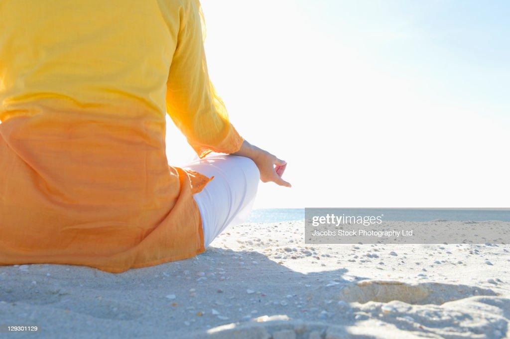 Mixed race woman practicing yoga on beach : Stock Photo