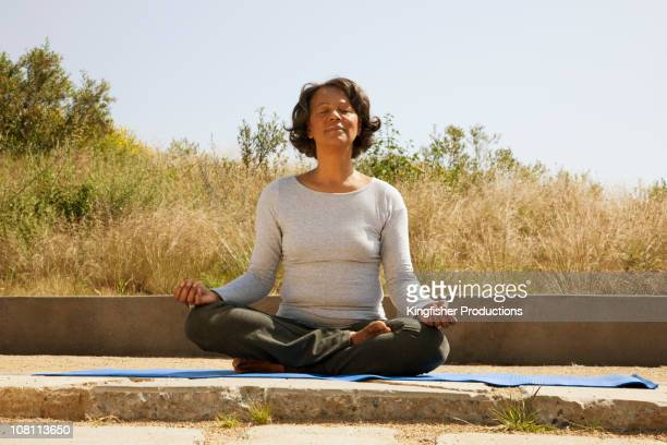 Mixed race woman practicing yoga outdoors