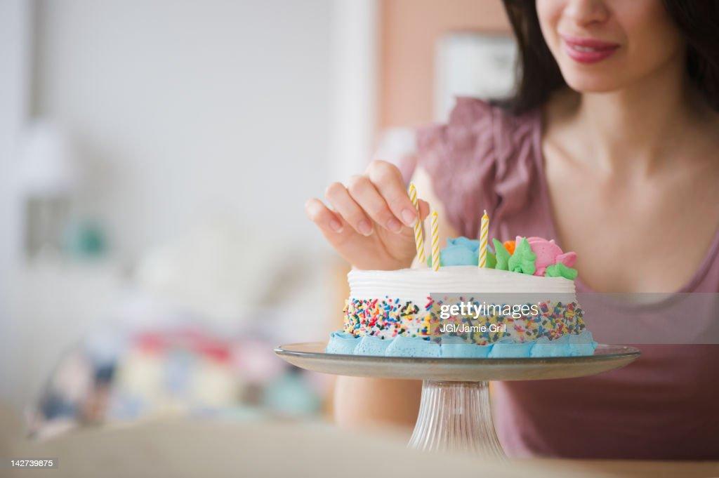 Mixed race woman preparing birthday cake : Stock Photo