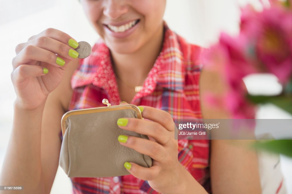 Mixed race woman putting coin into purse