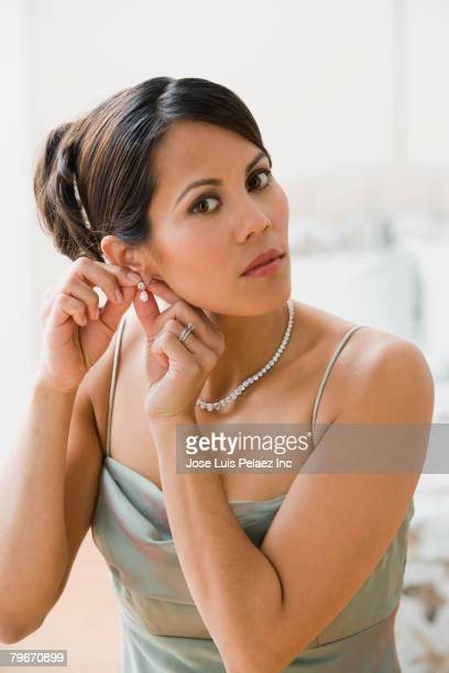 Mixed Race woman putting on earring