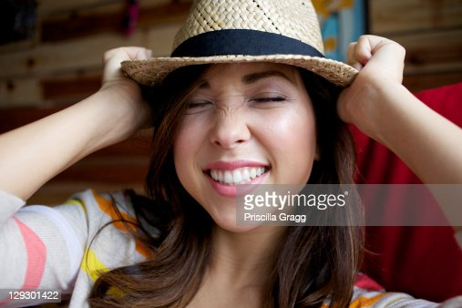 Mixed race woman putting on hat : Stock Photo