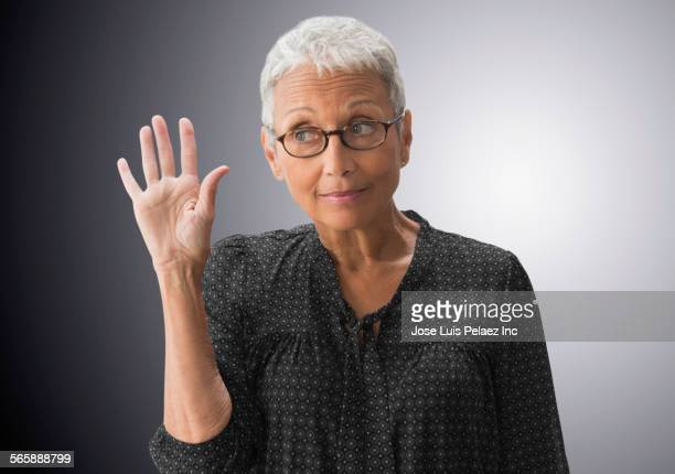 Mixed race woman raising her hand