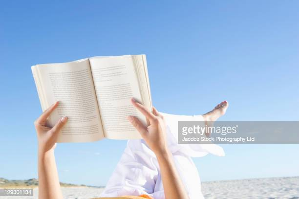 Mixed race woman reading book on beach