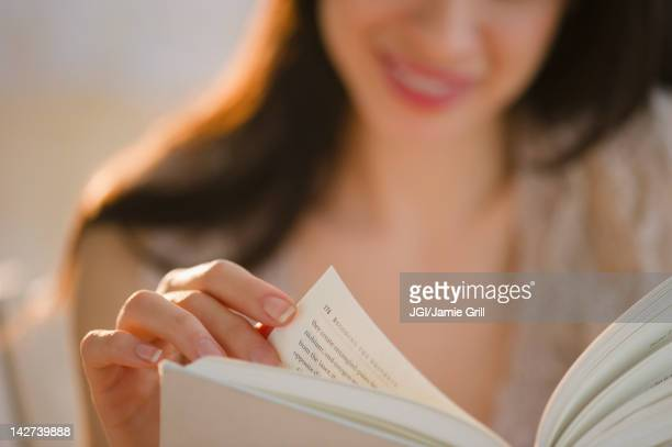 Mixed race woman reading book