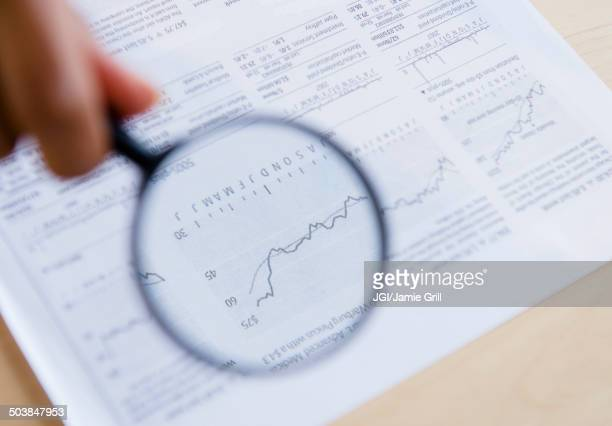 Mixed race woman reading graph with magnifying glass