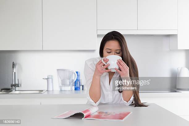 Mixed race woman reading magazine in kitchen