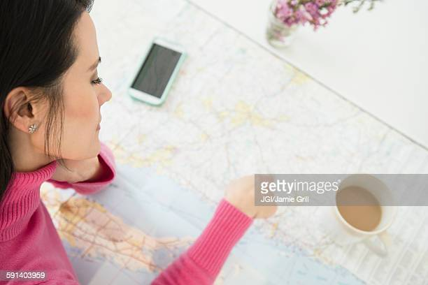 Mixed race woman reading roadmap with coffee