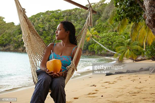 Mixed race woman relaxing in hammock on beach