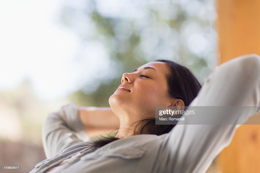 Mixed race woman relaxing on patio : Stock Photo