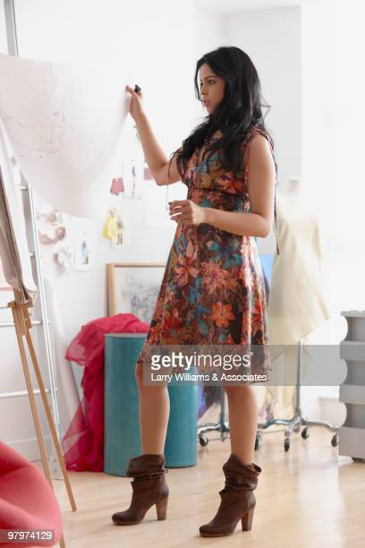 Mixed race woman reviewing sketch in design studio