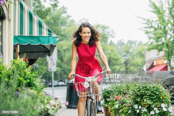 Mixed race woman riding bicycle in city