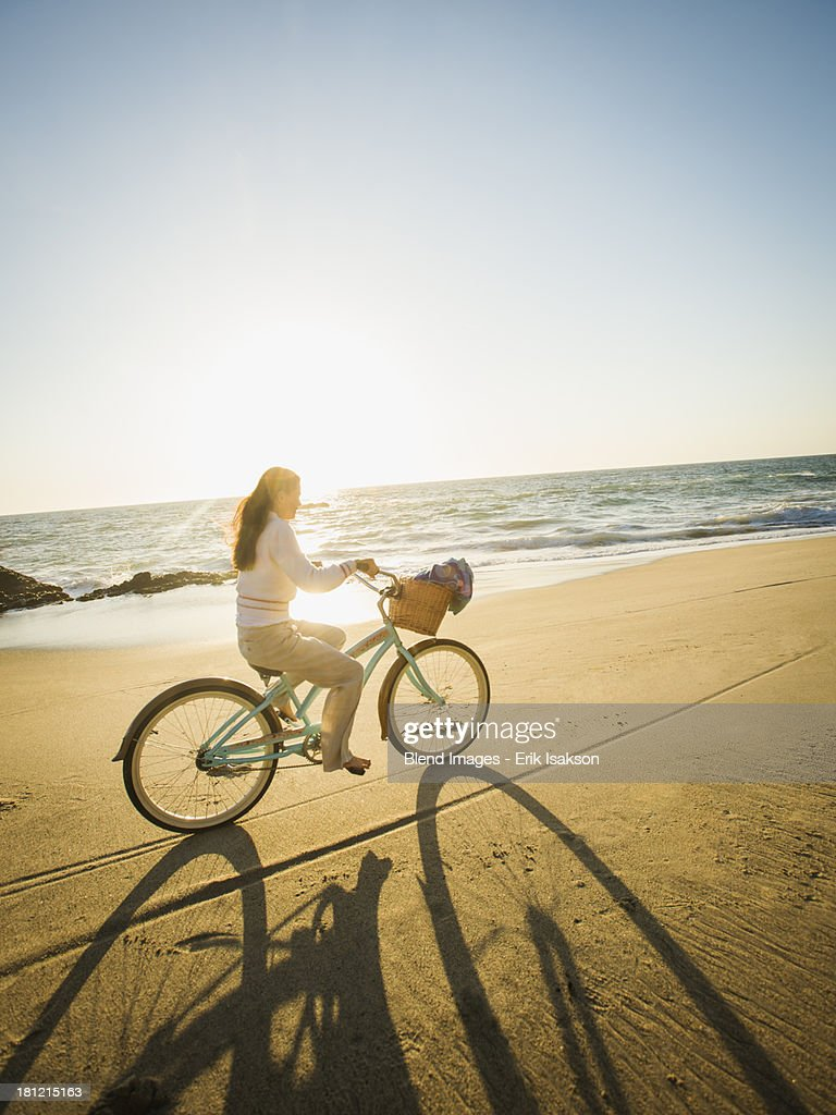 Mixed race woman riding bicycle on beach : Stock Photo
