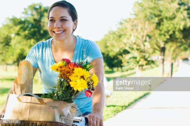 Mixed race woman riding bicycle with flowers in basket