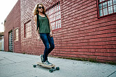 Mixed race woman riding skateboard on city street