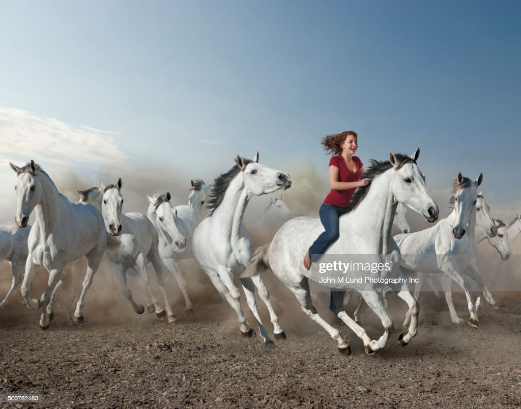 Mixed race woman riding wild horse in desert