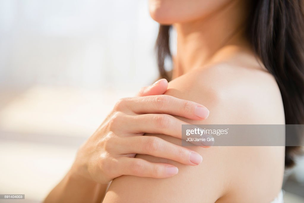 Mixed race woman rubbing lotion into skin : ストックフォト