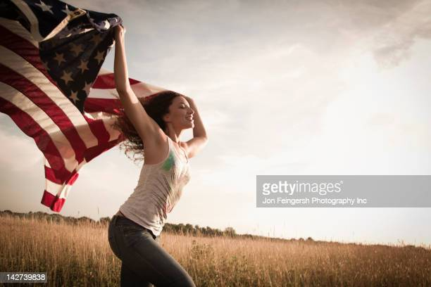 Mixed race woman running in field with American flag