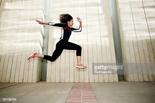 Mixed race woman running on city street