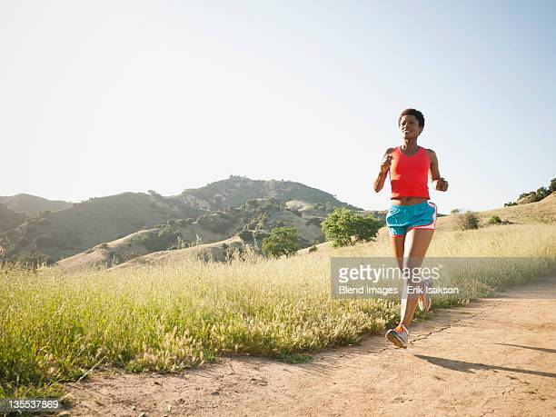 Mixed race woman running on remote trail