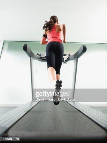 Mixed race woman running on treadmill