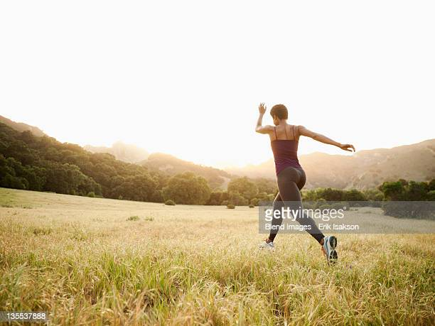 Mixed race woman running through remote field