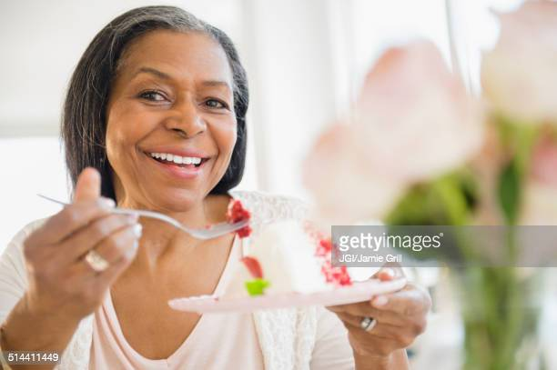 Mixed race woman sharing cake