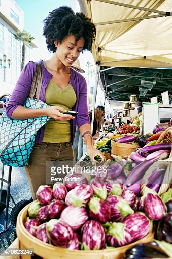 Mixed race woman shopping at vegetable stand : Stock Photo