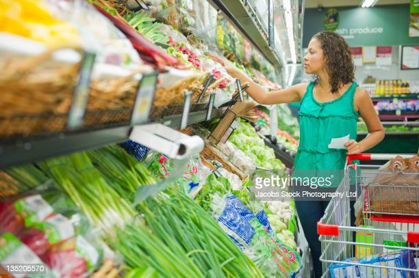 Mixed race woman shopping for vegetables