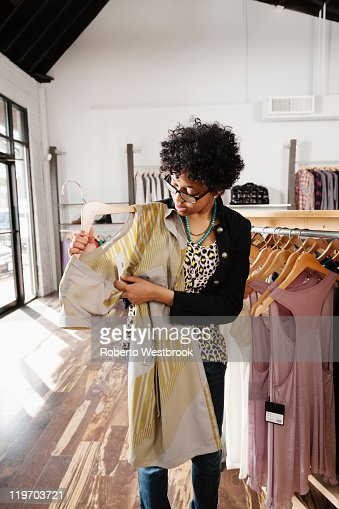 Mixed race woman shopping in clothing store