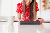 Mixed race woman shopping online in kitchen