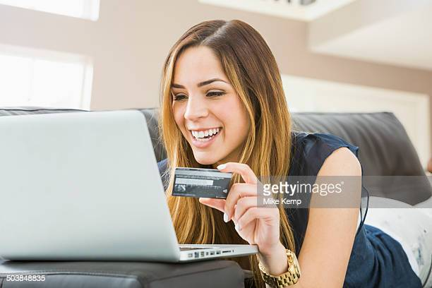 Mixed race woman shopping online on sofa