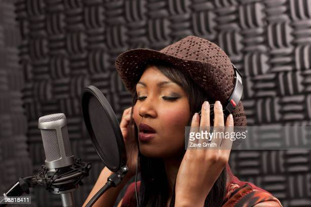 Mixed race woman singing in recording studio