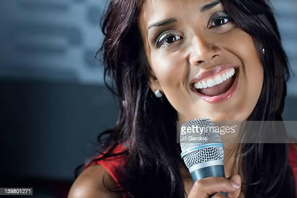 Mujer de raza mixta de música karaoke en club nocturno