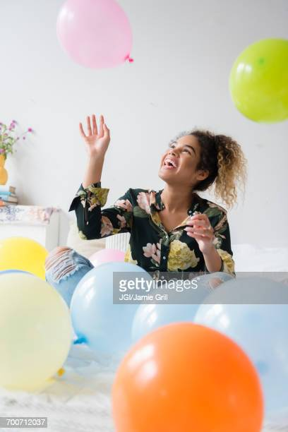Mixed Race woman sitting on bed playing with balloons
