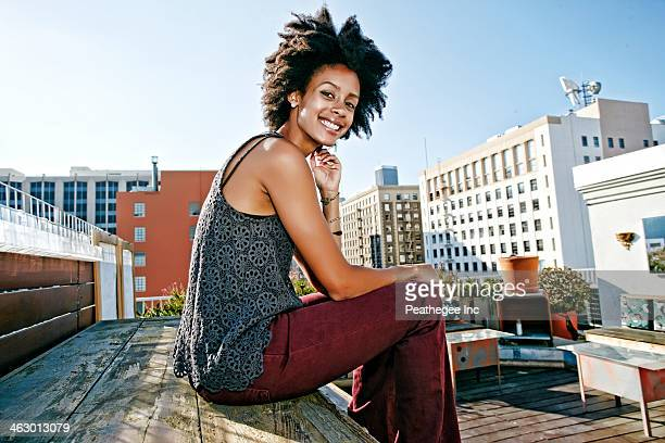 Mixed race woman sitting on urban rooftop