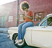 Mixed race woman sitting on vintage car