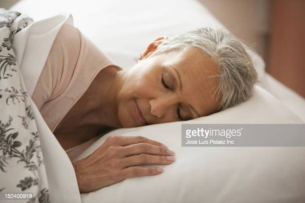 Mixed race woman sleeping in bed