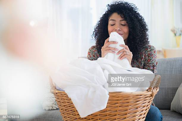 Mixed race woman smelling clean towels in laundry