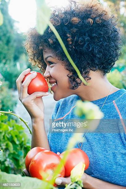 Mixed race woman smelling tomatoes in garden