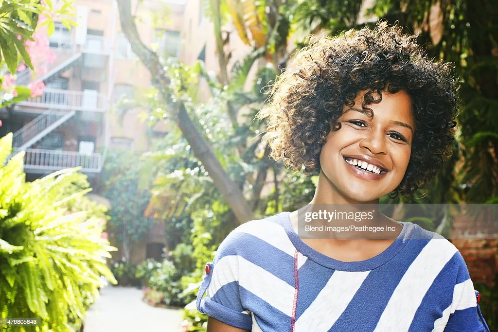 Mixed race woman smiling in courtyard : Stock Photo